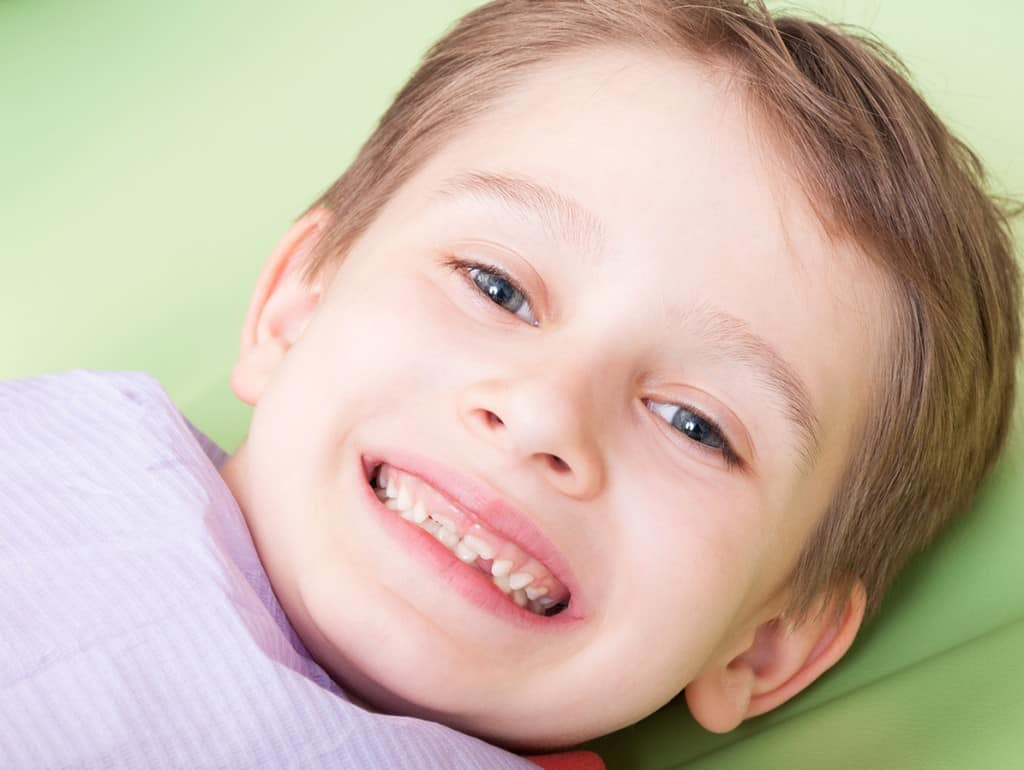 young white boy smiling in dental chair